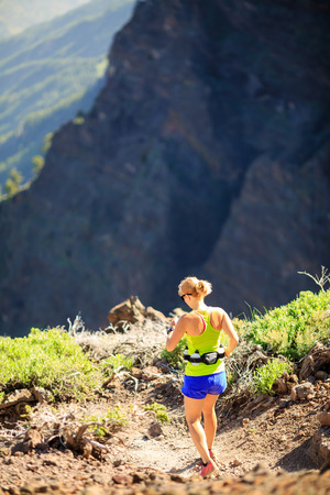 power walking: Young woman running or power walking in the mountains on sunny summer day. Beautiful natural landscape and female runner jogging exercising outdoors in nature rocky footpath trail on La Palma Canary Islands