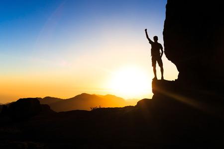 escalando: Silueta del hombre que sube explorando senderismo en las montañas puesta de sol y vistas al mar. Hombre caminante con mochila en la cima de una montaña que mira hermoso paisaje nocturno.