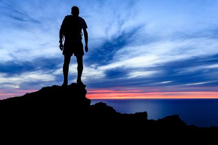 Man Wandern in den Bergen silhouette Sonnenuntergang und das Meer über schönen blauen Himmel. Männlichen Wanderer auf dem Gipfel eines Berges Blick auf Schönheit Nacht-Landschaft. Standard-Bild