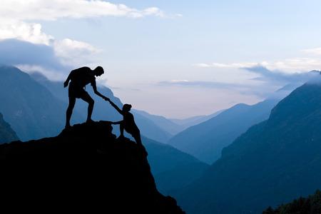 支援の手を助けるチームワーク カップル信頼山日没のシルエット。登山者の男性と女性のハイカーのチームは登山支援の上にお互いを助けるヒマラ