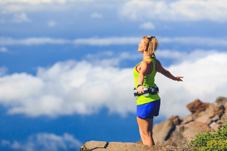 Happy woman runner joyful with arms raised outstretched smiling and ecstatic happiness with eyes closed. Fitness and exercise in summer meditation mountains nature outdoors freedom concept.
