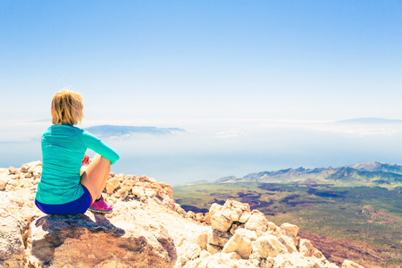 Young woman looking outside and meditation inspirational landscape of beautiful natural environment Fitness and exercising motivation and inspiration in sunny mountains over blue sky and ocean sea. Stock Photo