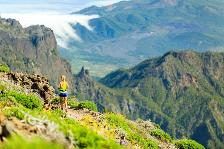 hiking trail: Young woman running or power walking in the mountains on sunny summer day. Beautiful natural landscape and female runner jogging exercising outdoors in nature rocky footpath trail on La Palma Canary Islands