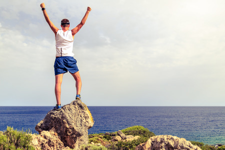 arm of a man: Happy trail runner success running or hiking achievement accomplishment business concept with man looking over the ocean horizon celebrating with arms outstretched raised up cross country running outdoors Stock Photo