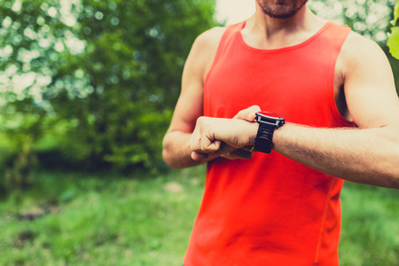 a check: Runner on mountain trail checking SportWatch looking at smart watch cross country runner checking the performance of GPS position pulse or heart rate. SmartWatch sports and fitness equipment in use outdoors in nature on summer trail
