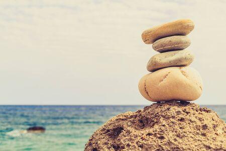 armonia: Equilibrio Piedras y bienestar concepto de spa de inspiración retro zenlike y bienestar composición tranquilo. Primer plano de guijarros blancos pila sobre el mar azul Foto de archivo