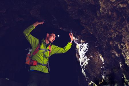 cueva: Hombre caminando y explorar una cueva oscura con luz subterráneo del faro. Explorador misterioso descubrimiento profundo túnel oscuro mirando misterio de mal humor en la pared de roca en el interior.
