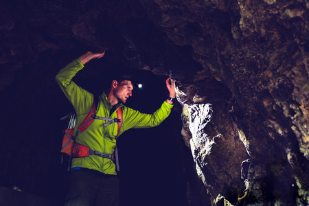 Man walking and exploring a dark cave with light headlamp underground. Mysterious explorer discovering deep dark tunnel looking moody mystery on rock wall inside.