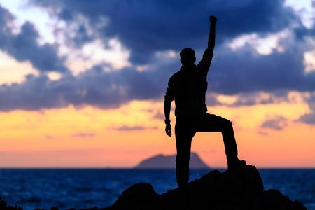 Erfolg, Leistung, Laufen oder Wandern Erfüllung Geschäft und Motivation Konzept mit Mann Sonnenuntergang Silhouette feiert mit Arme nach oben angehoben ausgestreckten Trekking Klettersteig in der Natur im Freien laufen