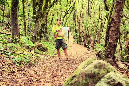 Man hiking hiker walking in green forest. Young male looking at maps and planning trip or get lost in the magical inspiration of beautiful green forest landscape of La Gomera Canary Islands. Adventure and motivation navigation concept.