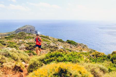Berglopen man crosscountry loopt in de bergen op een mooie zomerse dag. Training en uit te werken fitness gezonde kleurrijke runner joggen en te oefenen buiten in de natuur rotsachtig voetpad op Kreta Griekenland Stockfoto