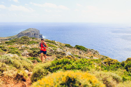 trails: Trail running man crosscountry running in mountains on a beautiful summer day. Training and working out fitness healthy colorful runner jogging and exercising outdoors in nature rocky footpath on Crete Greece Stock Photo