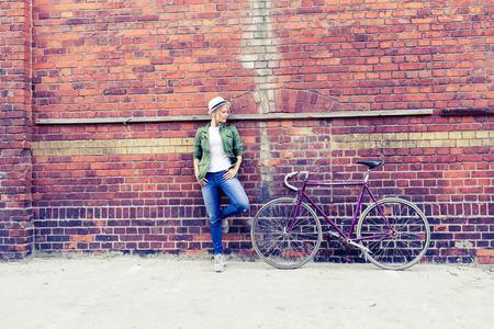 ciclismo: Hermosa joven inconformista con la bici de carretera de la vendimia en escena urbana de la ciudad. Mujer de ciclismo en bicicleta de pi��n fijo en la ciudad retro calle de la ciudad industrial de fondo.