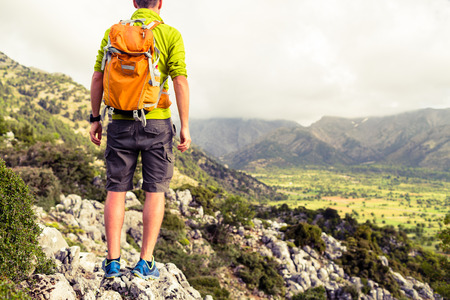 trekker: Hiking tourist man looking at beautiful mountains inspirational landscape. Hiker trekking with backpack on rocky trail footpath. Healthy fitness lifestyle outdoors concept. Stock Photo
