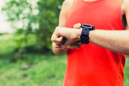 Runner on mountain forest trail looking at sportwatch smart watch, cross country runner checking performance, GPS position or heart rate pulse. Sport smartwatch and fitness equipment in use outdoors in nature on summer trail Stock Photo