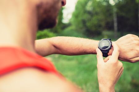 Runner auf Bergwaldpfad Überprüfung Blick in Sportwatch Smart Watch, Langläufer Kontrolle Leistung, GPS-Position oder der Herzfrequenz Puls. Sport Smartwatch und Fitnessgeräte im Einsatz draußen in der Natur auf Sommerweg