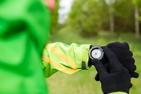 Hiker looking at electronic compass, sport gps smart watch. Man checking direction on smartwatch, navigation equipment. Hiking healthy sport and fitness outdoors in nature. photo
