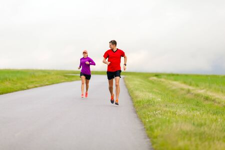 power walking: Man and woman two people runners running on country road fitness healthy lifestyle sport training speed beautiful landscape. Young couple training and doing power walking workout exercising outdoors in nature.