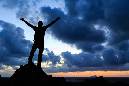 Success achievement silhouette hiking accomplishment business concept with man celebrating with arms up raised outstretched faith worship outdoors