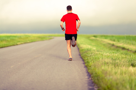power walking: Man running on country road fitness healthy lifestyle sport training speed beautiful landscape. Young runner jogging training and doing power walking workout exercising outdoors in nature. Stock Photo