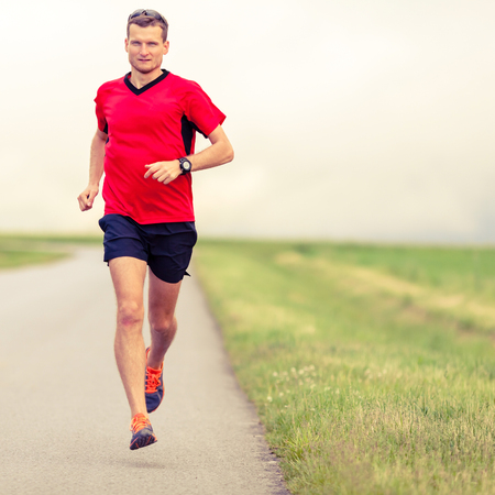 country lifestyle: Man running on country road fitness healthy lifestyle sport training speed beautiful landscape. Young runner jogging training and doing power walking workout exercising outdoors in nature. Stock Photo