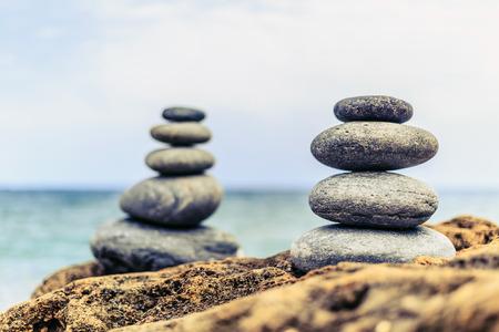 equilibrio: Equilibrio Piedras y bienestar concepto de spa retro pacífica y único zenlike inspiración y bienestar composición tranquilo. Primer plano de guijarros blancos pila sobre el mar azul Foto de archivo