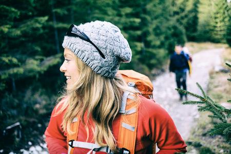 男と女のハイカー バックパック緑の森山の道で歩いて。若いカップル キャンプ、田舎道、美しい感動的な風景の中の健康的なライフ スタイルでト 写真素材