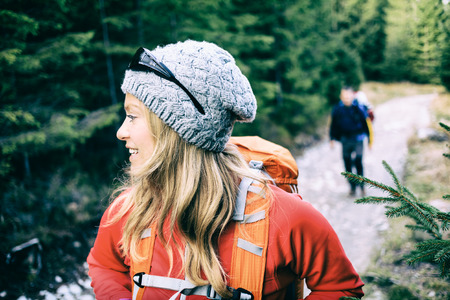 alps: Man and woman hikers walking with backpacks on trail in green forest mountains. Young couple camping and trekking on country road, healthy lifestyle in beautiful inspirational landscape. Weekend vacations in Tatra Mountains, Poland.
