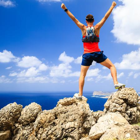 成功動機幸せな男して実行やハイキング、達成成功と幸福の概念、両手を上げ伸ばし登山やトレイル ランニング、屋外を健康な生活様式を祝う男