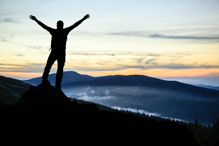 Success and achievement, hiking man silhouette concept with climber with arms up, outstretched on mountains peak, healthy lifestyle at sunset