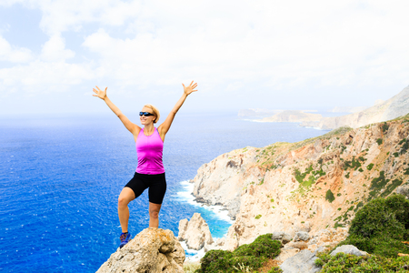 hiking: Success achievement climbing or hiking accomplishment concept, woman trail runner celebrating with arms up raised outstretched hiking, climbing or cross country running healthy lifestyle Stock Photo