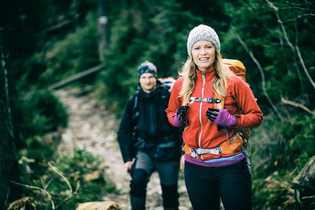 Mann und Frau, glückliches Paar Wanderer Trekking in grün Herbst Wald und Berge. Junge Menschen zu Fuß auf Weg mit Rucksäcken, gesunden Lebensstil Abenteuer, Camping auf Wanderung, alten Vintage-Foto-Stil.