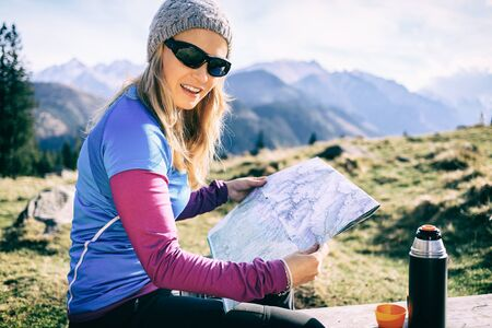 trekker: Young woman hiker reading and checking map in mountains on hiking trip. Healthy lifestyle fitness girl camping on winter trip drinking coffee or tea and looking at beautiful inspirational landscape view in Tatras, Poland.