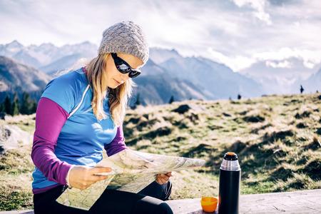 若い女性ハイカー読書とハイキングの山の地図をチェックします。健康的なライフ スタイル フィットネス女の子がコーヒーやお茶を飲んだとポーラ