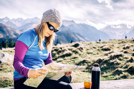Young woman hiker reading and checking map in mountains on hiking trip. Healthy lifestyle fitness girl camping on winter trip drinking coffee or tea and looking at beautiful inspirational landscape view in Tatras, Poland.