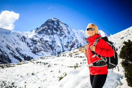 Woman hiker nordic walking, healthy lifestyle in Himalaya Mountains in Nepal. Trekking and hiking on snow white winter nature, beautiful inspirational mountain landscape.