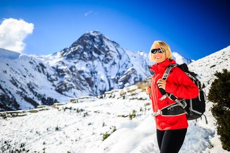 Vrouw wandelaar nordic walking, gezonde levensstijl in Himalaya gebergte in Nepal. Trekking en wandelen in de sneeuw winter wit natuur, mooi inspirerend berglandschap.