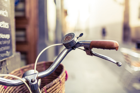 City bicycle handlebar and basket over blurred background, bike cycling on city urban streets, commute retro concept in town Фото со стока