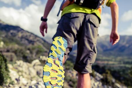 ハイキングや感動的な風景の美しい山々 で男を実行しています。スポーツ シューズと岩の歩道での人の足の裏。ハイカーのバックパックとトレッキ