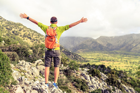 Happy climber hiker winning reaching life goal, success man at summit, successful business concept. Young runner hiker arms up outstretched, freedom and happiness rock climbing achievement in mountains 写真素材