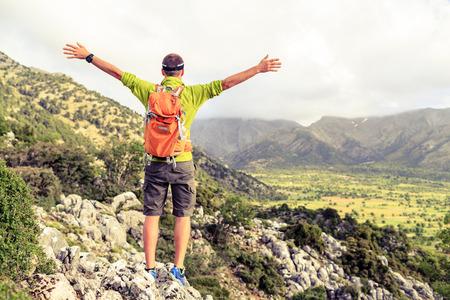 Erfolg: Glücklicher Bergsteiger Wanderer winning Erreichen Lebensziel, Erfolg Mann am Gipfel, erfolgreiche Business-Konzept. Junge Läufer Wanderer Arme nach oben ausgestreckt, Freiheit und Glück Klettern Leistung in den Bergen