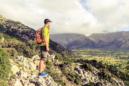 Hiking man looking at beautiful mountains inspirational landscape. Hiker trekking with backpack on rocky trail footpath. Healthy fitness lifestyle outdoors concept. 写真素材