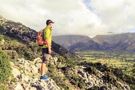 Wandelen man op zoek naar prachtige bergen inspirerende landschap. Wandelaar trekking met rugzak op rotsachtig pad voetpad. Gezonde fitness lifestyle buiten concept. Stockfoto