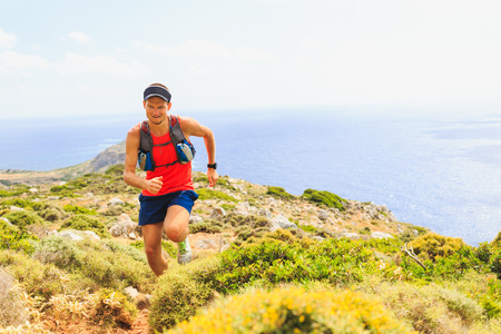 Trail running man cross country running in mountains on summer beautiful day. Training and working out runner jogging and exercising outdoors in nature, rocky footpath on Crete, Greece