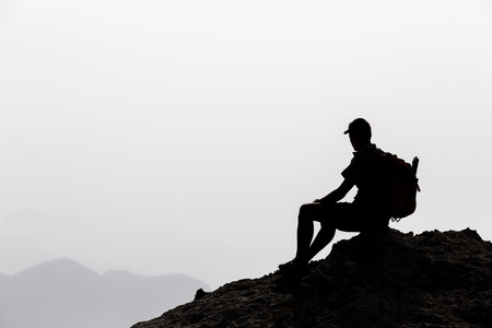 Man camping and hiking silhouette in mountains, inspiration and motivation concept. Hiker with backpack on top of rocky mountain looking at beautiful inspirational landscape. Stock Photo