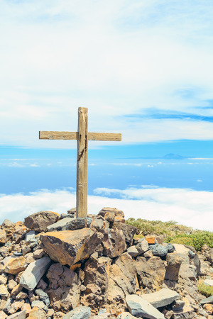 Christian cross on mountain top, rocky summit, beautiful inspirational landscape with ocean, island, clouds and blue sky, looking at scenic blue sea and white clouds. Stock Photo