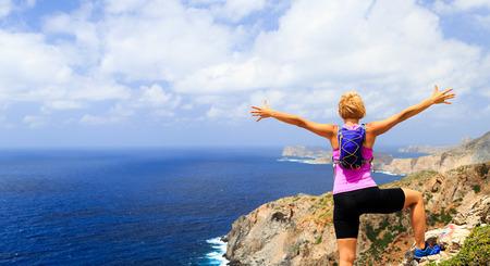Succes prestatie rennen, klimmen of wandelen prestatie concept, vrouw vieren met armen opgewekt uitgestrekte wandelen, klimmen of trailrunning gezonde levensstijl