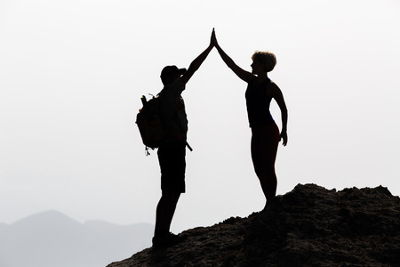 Successful couple achievement climbing or hiking, business concept with man and woman celebrating with arms up raised outstretched outdoors. Motivational and inspirationan silhouette landscape.