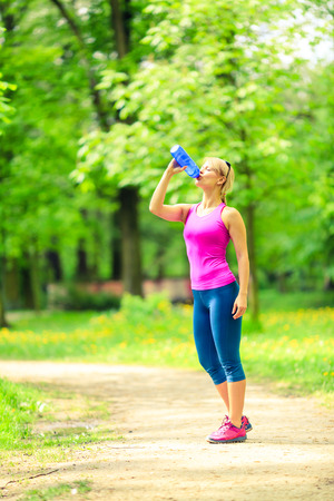 water sport: Woman runner running and drinking sports drink water in park when working out and training, healthy lifestyle, exercising on bright summer trail