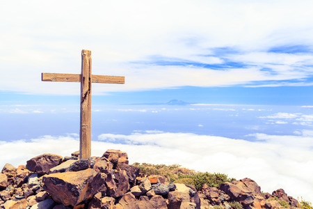 Christian wooden cross on mountain top, rocky summit, beautiful inspirational landscape with ocean, island, clouds and blue sky, looking at scenic blue sea and white clouds.